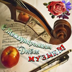 Яблоко и смычок на нотах на День музыки