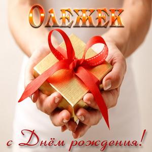 Картинка с подарком в женских руках Олегу на День рождения