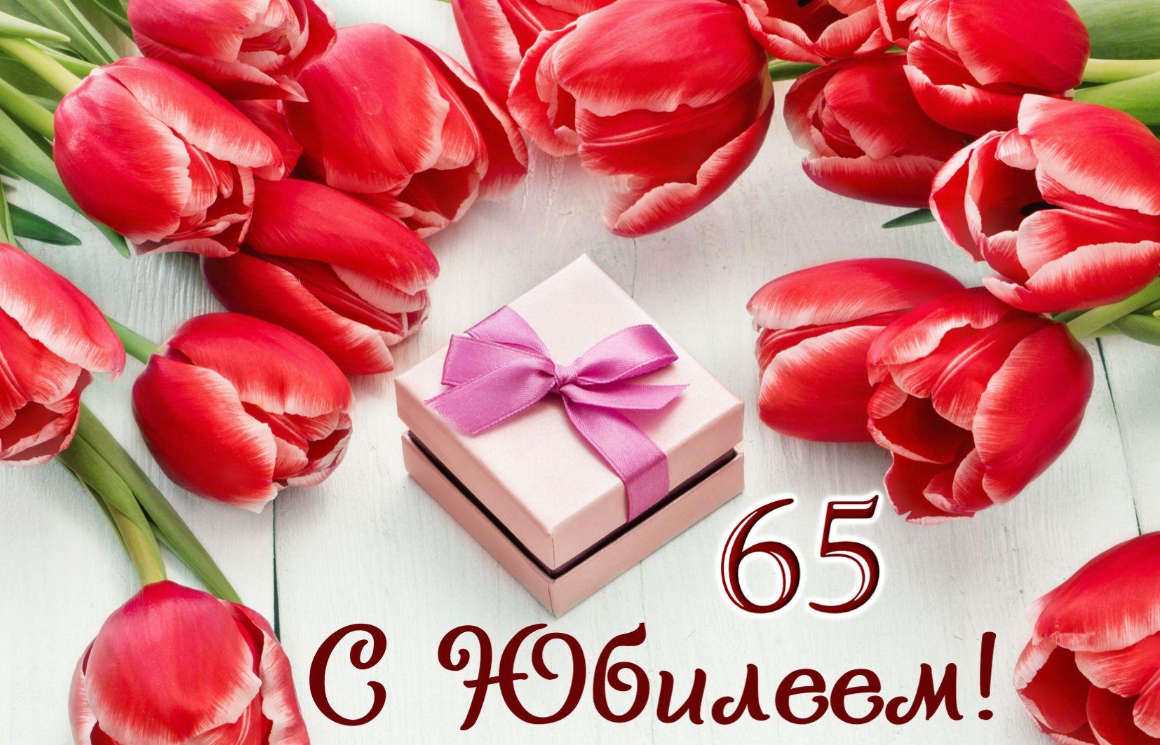Открытка на юбилей 65 лет - подарок в окружении красных тюльпанов